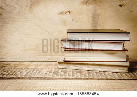 some old books on a wooden, dusty table