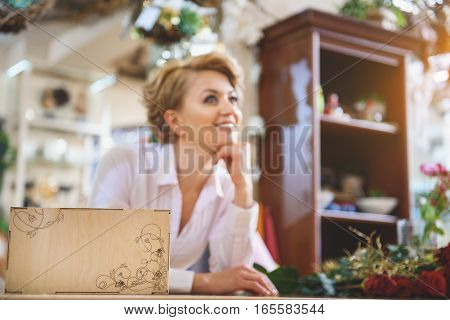 My small business is flourishing. Dreamful female florist is standing near counter and smiling. Focus on wooden box