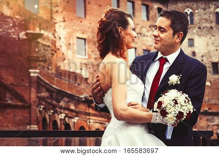 Husband and wife. Couple marriage. Newlyweds. Romance between a married couple with wedding gown. The women is holding a bouquet of flowers.