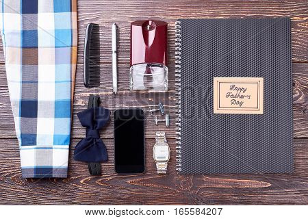 Notebook, greeting card and smartphone. Father's Day paper near accessories. Party look for dad.