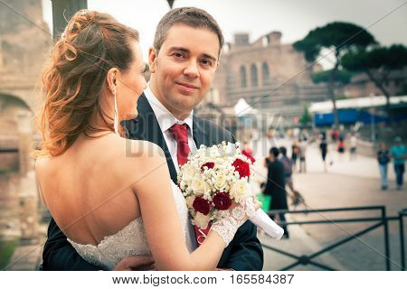 Couple newlyweds, husband and wife, hugging in the city. The women holding a bouquet of flowers in hand. The bride with wedding dress, showing her back. In the background, blurred, many tourists visiting the historic city of Rome, Italy.