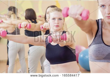 Portrait of Three Nice and Attractive Fitwomen Having a Stretching Workout With Barbelles Indoors Together.Horizontal Composition