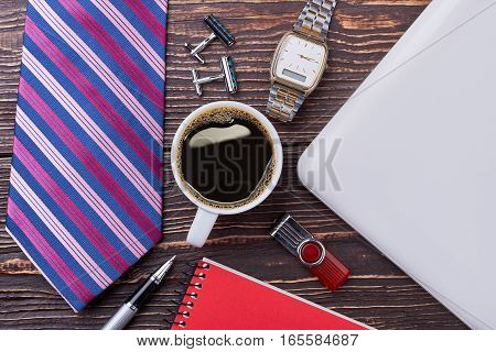 Tie, coffee and watch. Flash drive on wooden backdrop. Day in office.