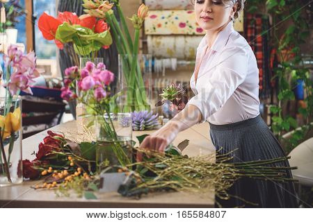 Skillful female florist is creating bouquet with inspiration. He is selecting plant from bunch carefully