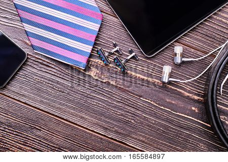 Cufflinks and striped necktie. Earphones and tablet on wood. Accessories of a successful man.