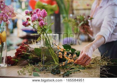 Close up of female hand is taking branch of rowan to join bunch of flowers. Focus on roses and other plants on table in flower shop
