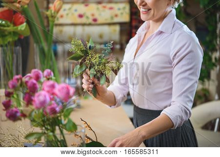 It will be wonderful bouquet. Inspired woman is holding bunch of plants and smiling