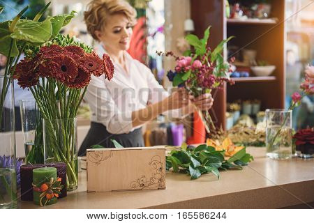 Successful female florist is creating bouquet with aspiration. She is holding bunch and smiling happily