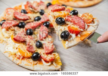 Cook takes a shovel one piece of pizza with cheese olives and salami mushrooms and tomatoes. On a wooden stand.