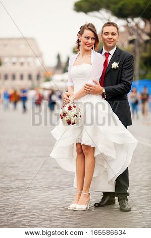 Newlyweds in the city. Happy married couple. They are located in the historic center of Rome, Italy. The women dressed in white holding a bouquet of flowers.