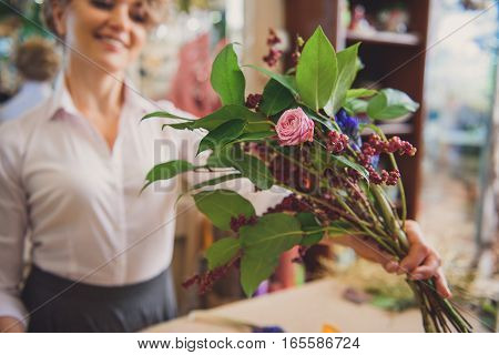 Joyful female florist is showing self-made bouquet to camera. She is standing and smiling. Focus on flowers