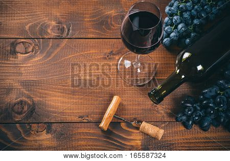Bottle And Glass Of Red Wine, Grape, Corkscrew And Cork On Wooden Background