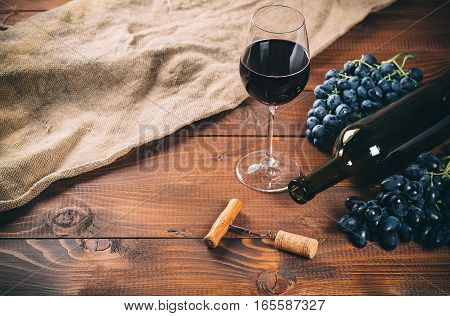 Bottle And Glass Of Red Wine, Grape, Corkscrew And Cork On Wooden Background With Burlap