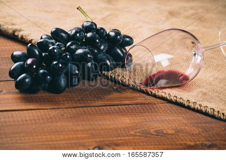 Glass Of Red Wine And Grape On Wooden Background With Burlap