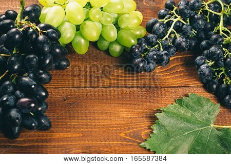 Bunch Of White And Blue Grapes With Leaves Over Burlap Napkin On Wooden Background