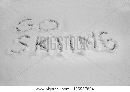 close up on Word go skiing written in snow