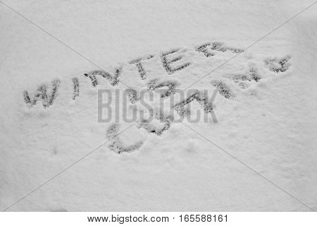 close up on Word winter is coming cold written in snow