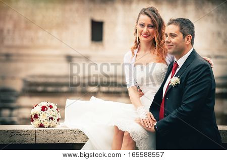Husband and wife. Couple marriage. Newlyweds. Romance between a married couple with wedding gown. The smiling women is sitting with a bouquet of flowers.