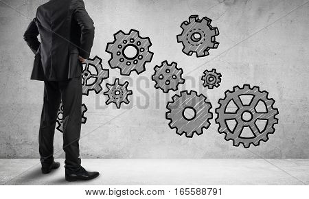 Back view of businessman looking at wall with drawn gear mechanism