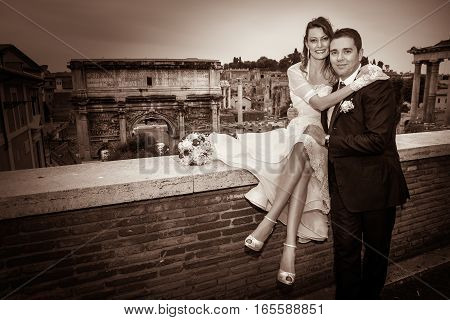 Husband and wife newlyweds. Couple marriage. The two married are located in the historic center of Rome, close to the Imperial Forums. The smiling women is sitting with a bouquet of flowers. Vintage colors.