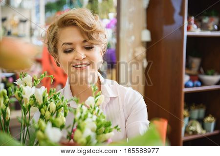 Professional female florist is choosing flowers for bouquet. She is standing and smiling happily