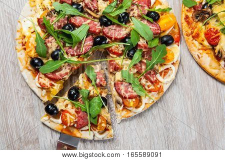 Cook takes a shovel one piece of pizza with cheese olives and salami mushrooms and tomatoes arugula. On a wooden stand.