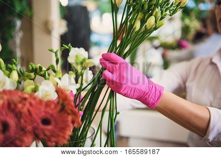 Close up of florist arms taking white flowers from vase