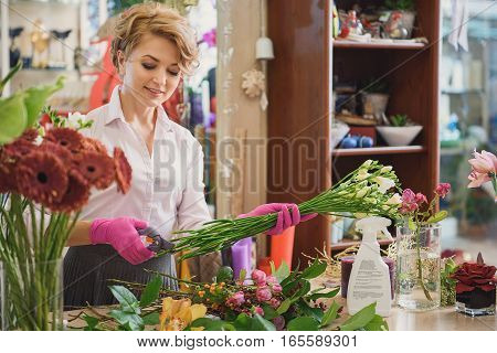 Joyful female florist is making bouquet at her store. She is cutting branches and smiling