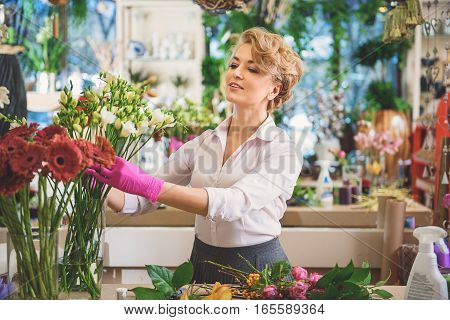 Inspired woman is creating masterpiece from flowers in shop. She is adjusting plants in vase and smiling