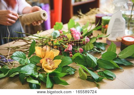 Close up of florist hands preparing rope for joining plants together. Focus on flowers on table