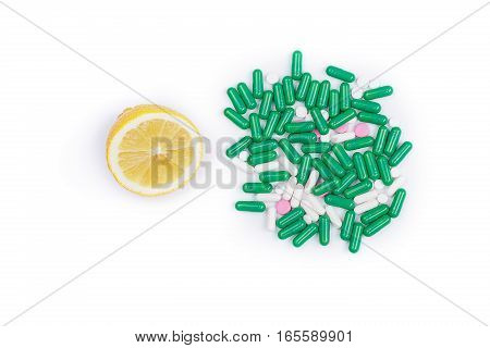 Lemon and pile of pills on a white background. The dilemma of what to choose