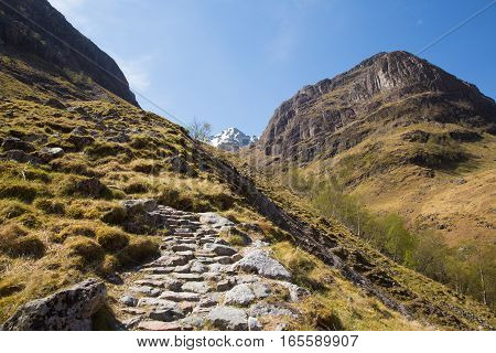 Path up to Glencoe snow topped mountains Scotland UK in Scottish Highlands in spring with blue sky and sunshine