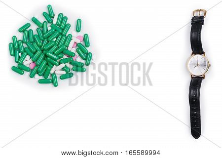 Watch lie down with pills on white background. Time taking a dose of pills