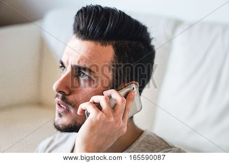 Portrait of a young man worried taking a phonecall on his smart phone in his home - Angry man in a bad mood having some discussion using cellphone
