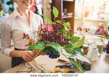Bouquet is ready. Happy woman is showing flowers to camera and smiling