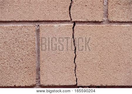foreground of a vertical crack on a wall of bricks
