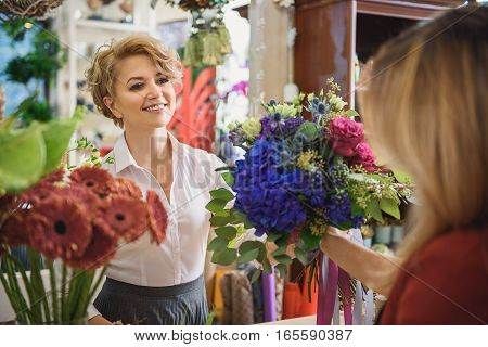 Take your order. Skillful florist is handing bouquet to her female customer. She is smiling with happiness