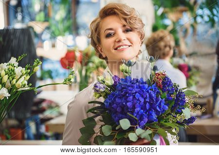 Happy female florist is holding bouquet and smiling