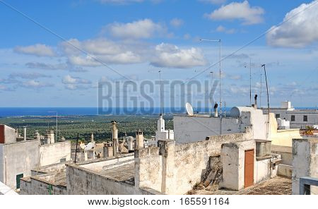 View on the roofs of Ostuni with antenna on olive fields and the blue Adriatic Sea Italy Europe with beautiful blue sky and white clouds