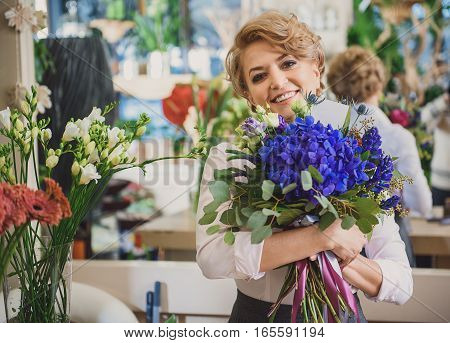 Happy florist is hugging wonderful blue bouquet with admiration. She is looking at camera and smiling