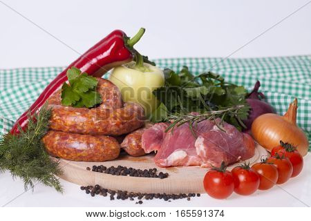 raw homemade sausages and fresh pork with vegetable and spices on the table
