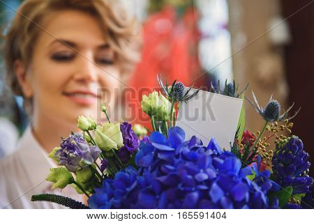 Skillful female florist is showing self-made bouquet to camera. She is smiling with satisfaction. Focus on card in flowers