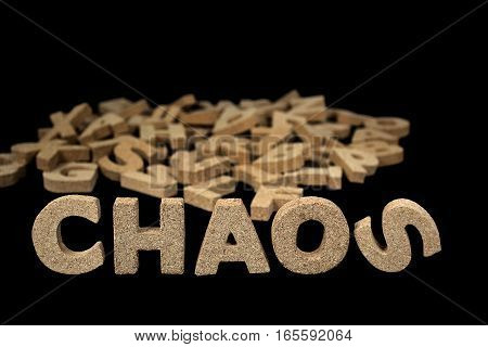 word chaos in block cork letters and jumbled alphabet on black