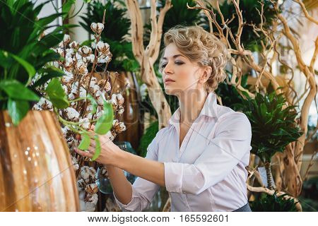 Professional female florist is caring of plant in store with concentration