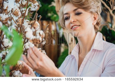 What a bountiful gift of nature. Excited woman is admiring on plant and smiling in flower shop