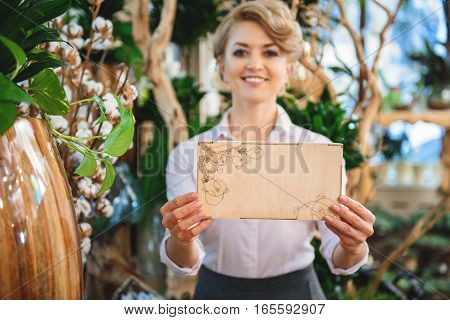 Excited female florist is showing wooden box with flower ornament and smiling