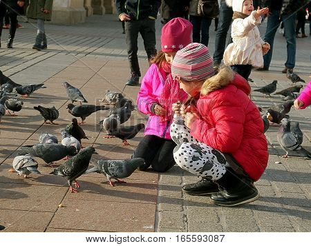 Kids and pigeons. Krakow, Poland - November 05, 2016 Girls nourish them pigeons on the Main Market Square in Krakow.