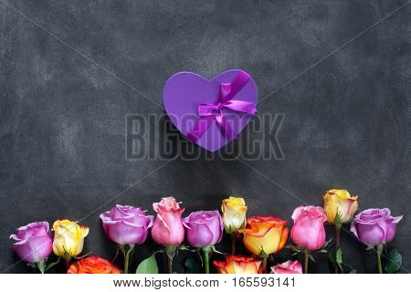 Purple and yellow roses, box present on black background. Overhead view with copy space. Horizontal orientation
