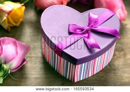 Box present on the forefront, purple and yellow roses on the background.