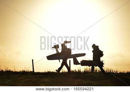 Two People Walking With Model Aircraft At Sunset